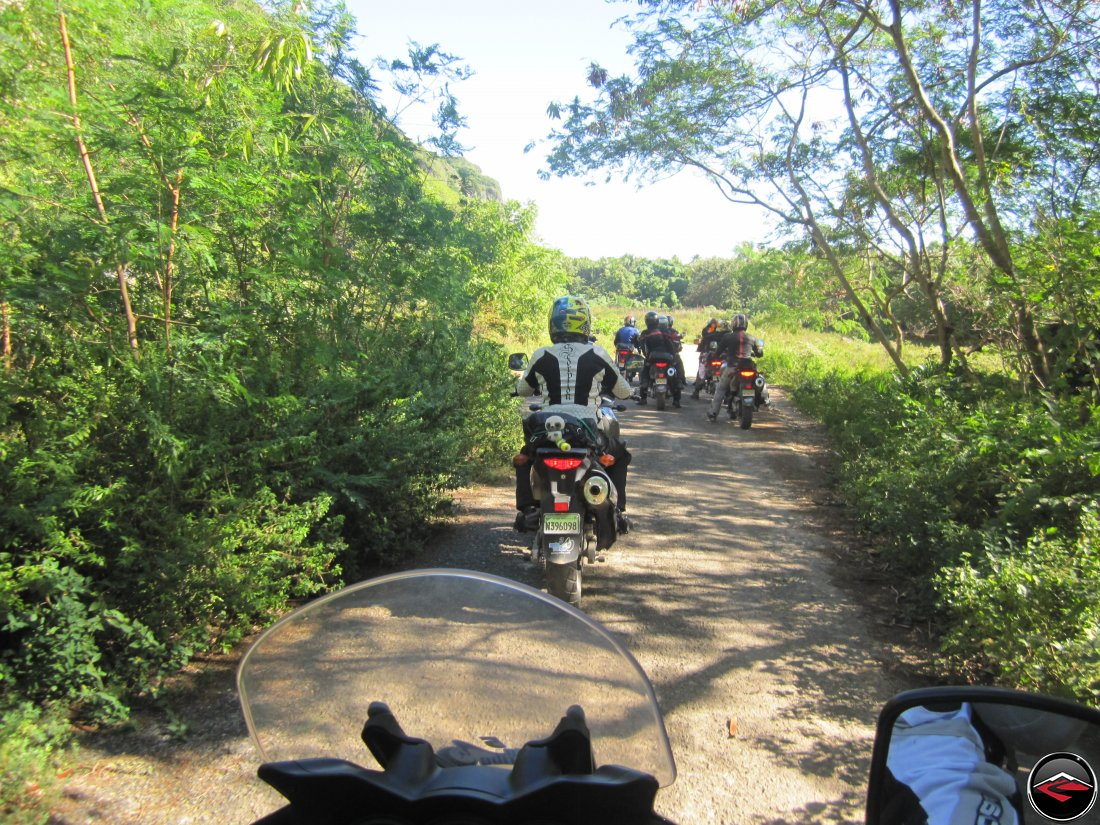 Group of motorcycles ride down a super narrow road through the jungle on a caribbean island
