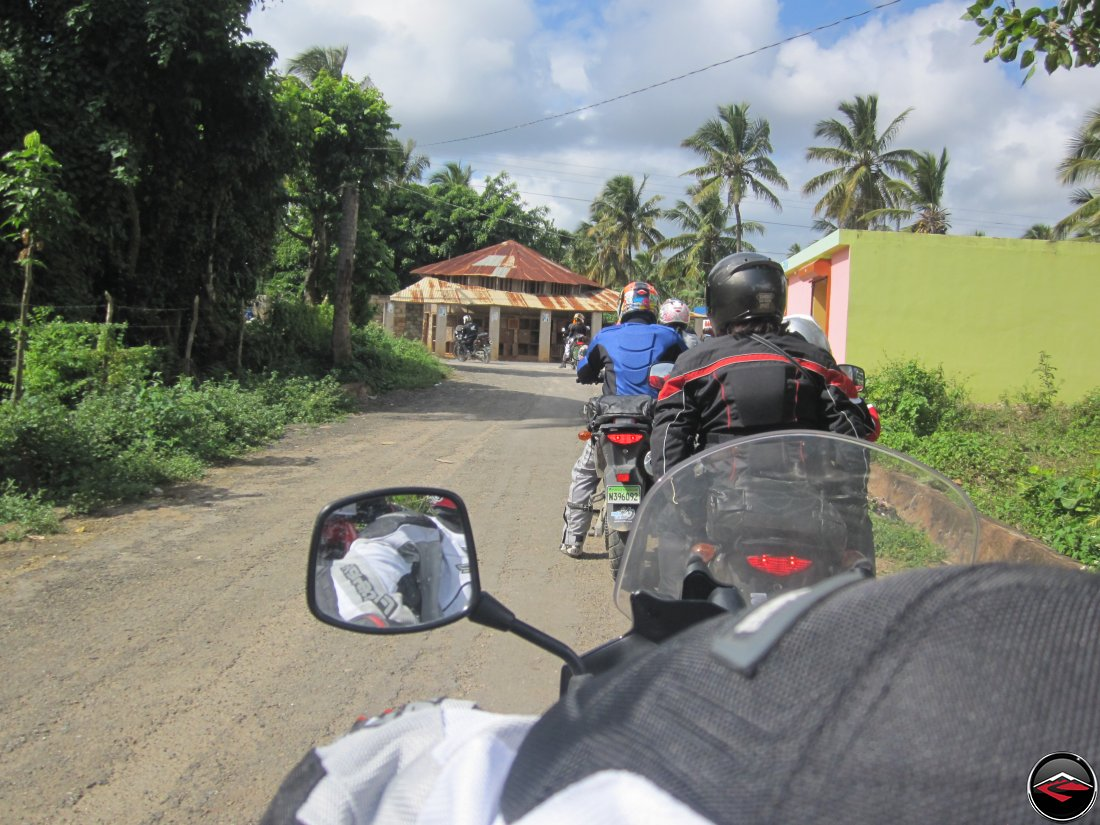 riding motorcycles past small dominican republic buildings