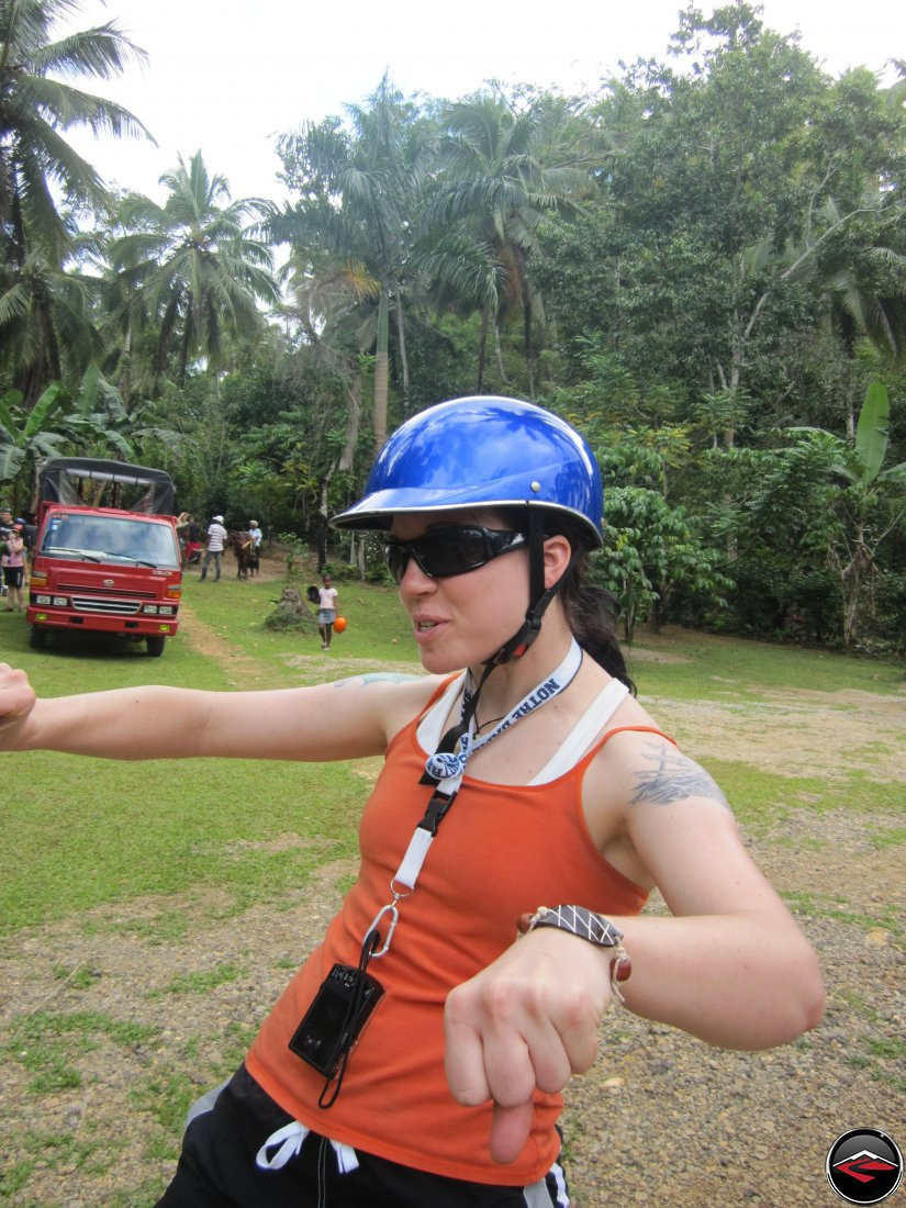 woman pretends to ride a chopper while wearing a silly helmet Cascada El Limon Dominican Republic