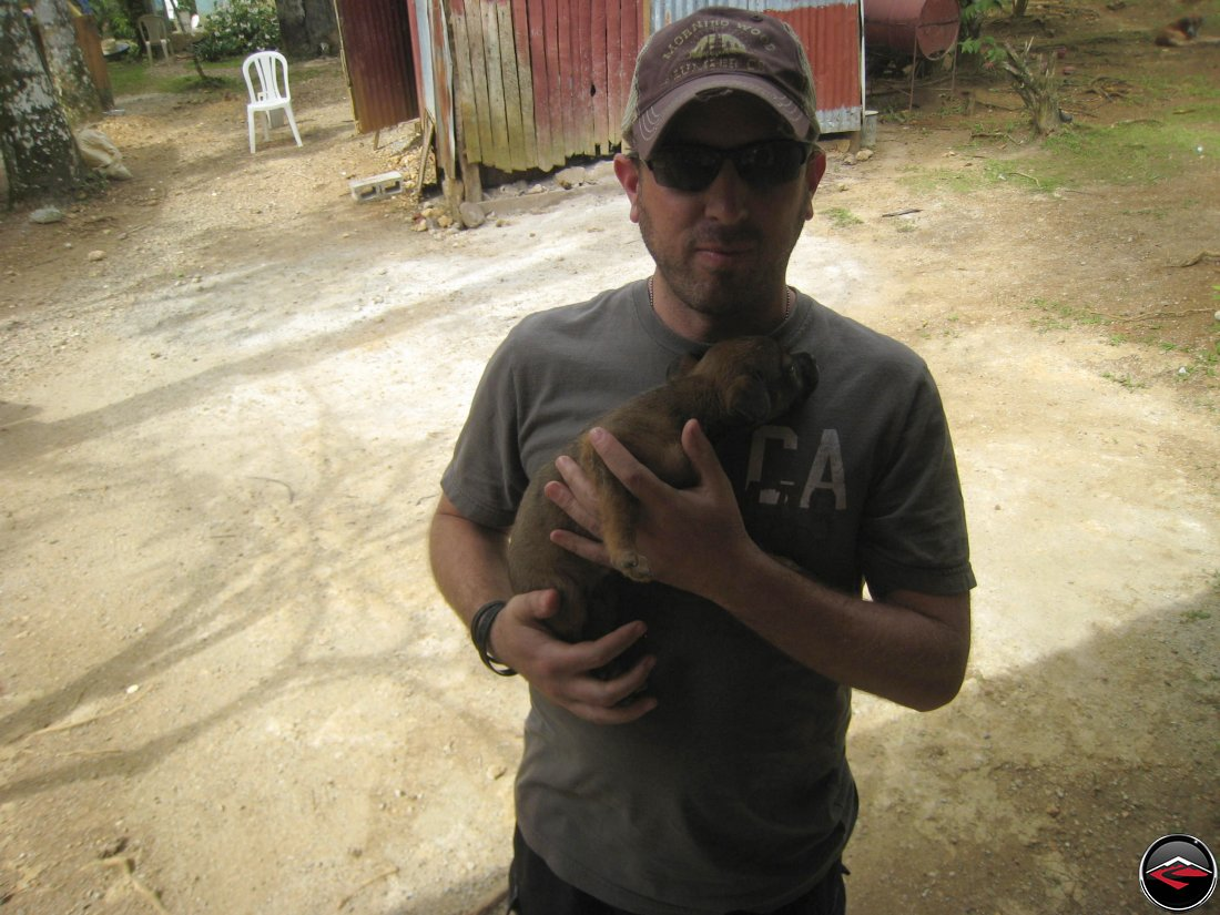 Man holds a stray puppy in the dominican republic