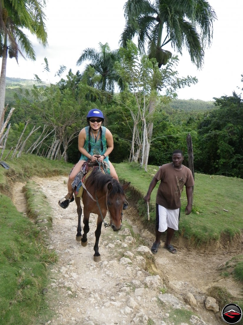 Woman riding a small horse on a caribbean island Cascada El Limon Dominican Republic