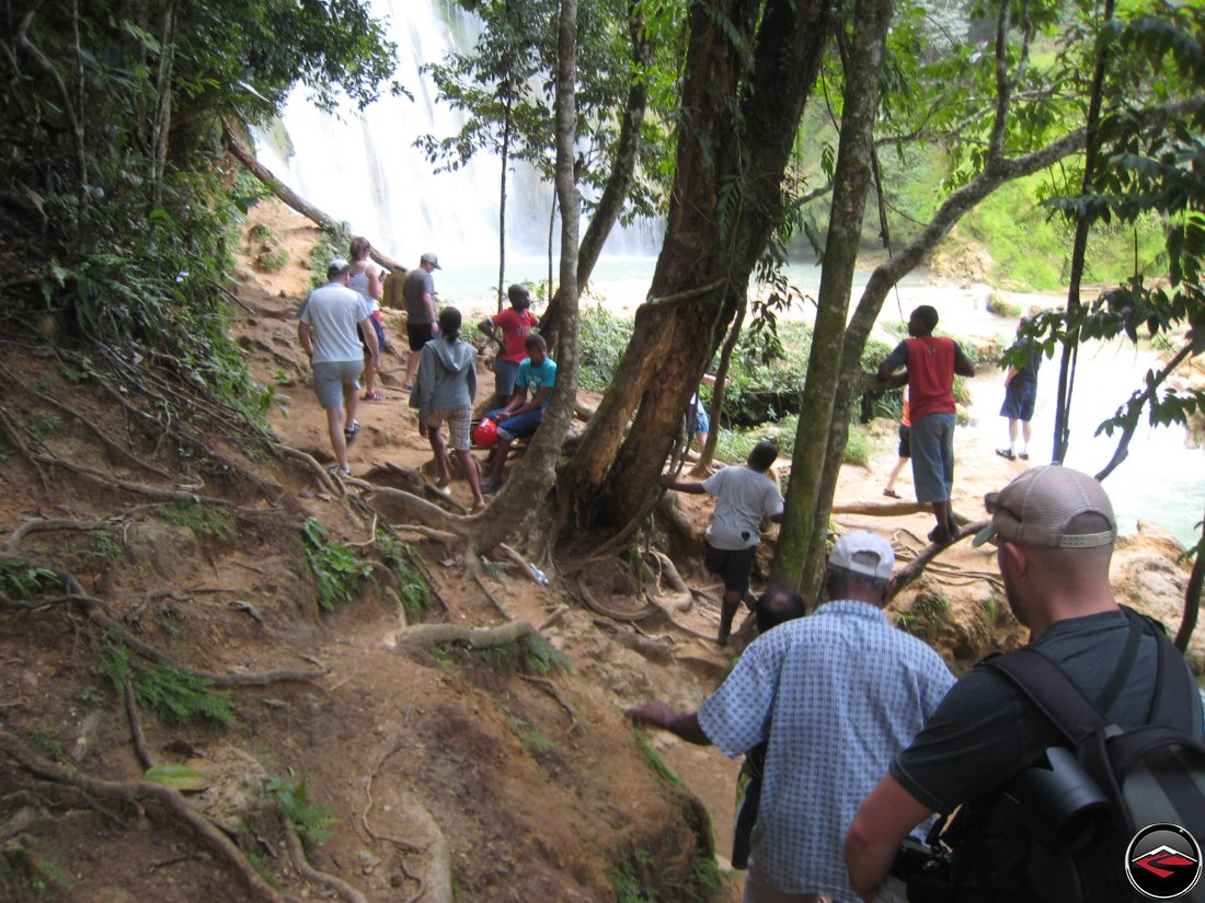People hiking down a hill, approaching the bottom of the waterfall Cascada El Limon Dominican Republic