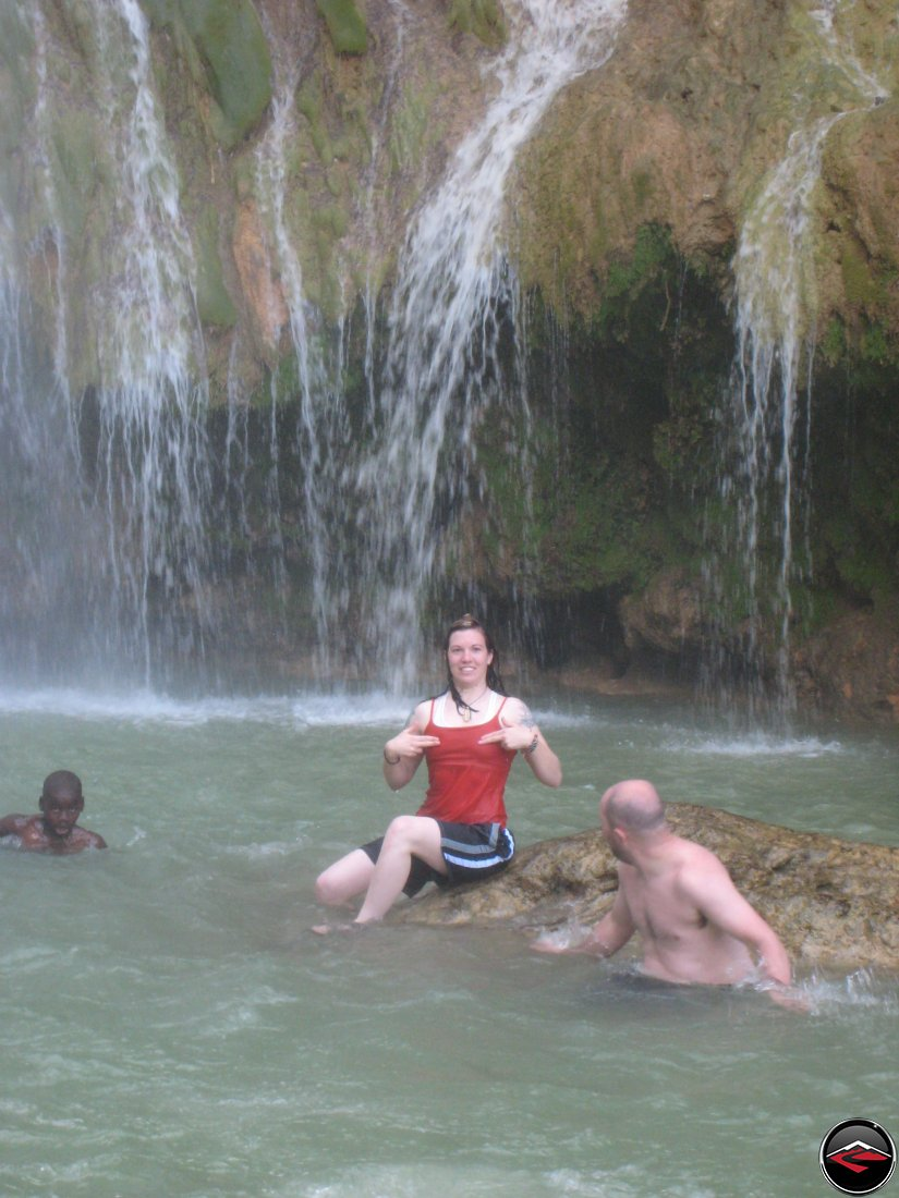 woman covering her nipples while sitting on a rock in front of a waterfall Cascada El Limon Dominican Republic
