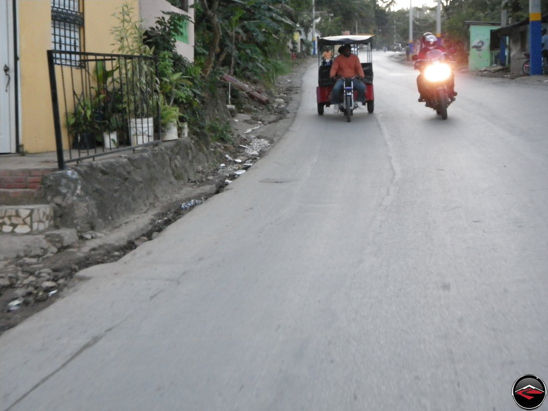 motorcycle passing a three-wheeled moto taxi on a caribbean island