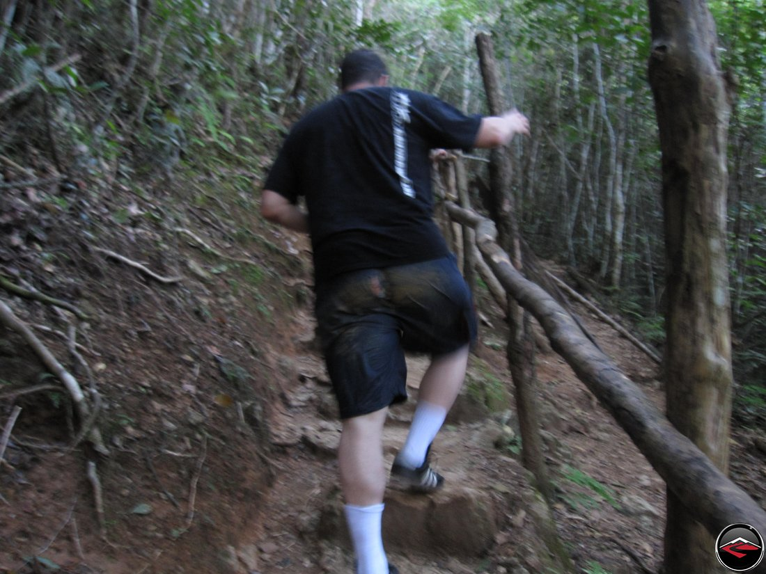 man with a hole in the butt of his shorts hiking up a steep hill Cascada El Limon Dominican Republic