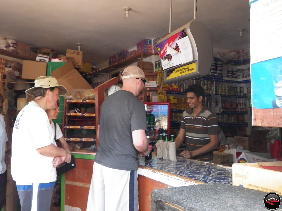 People at the counter of a small caribbean conveinence store