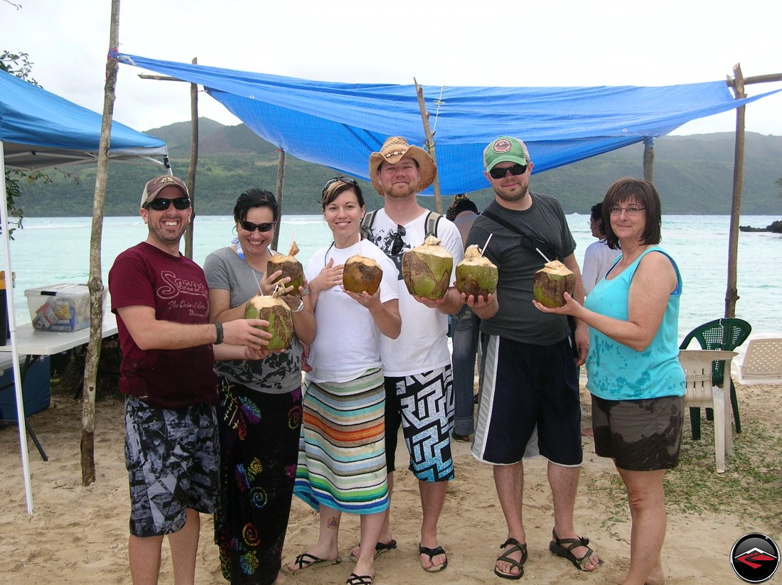 group of people standing on the beach holding pina colodas made out of coconut Playa Rincon Dominican Republics