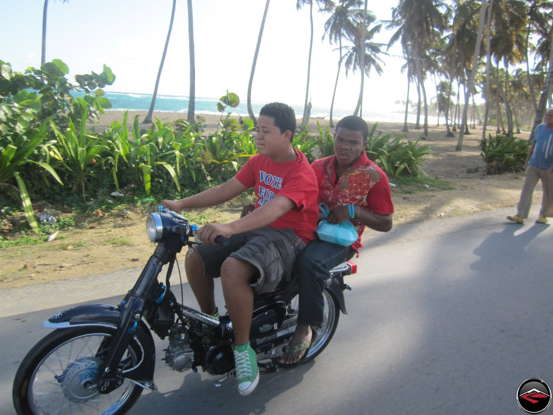 two men riding a honda super-cub in the dominican republic