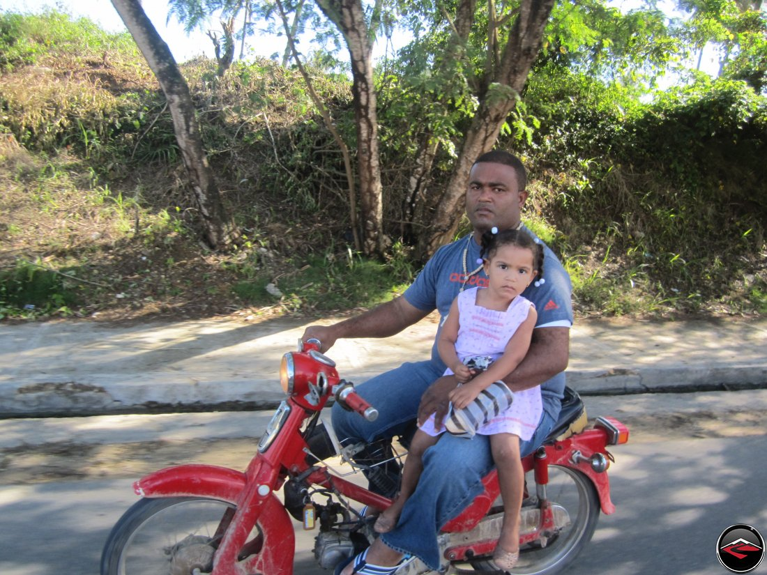 man riding a motorcycle with his daughter, a 3-year old girl, on his lap