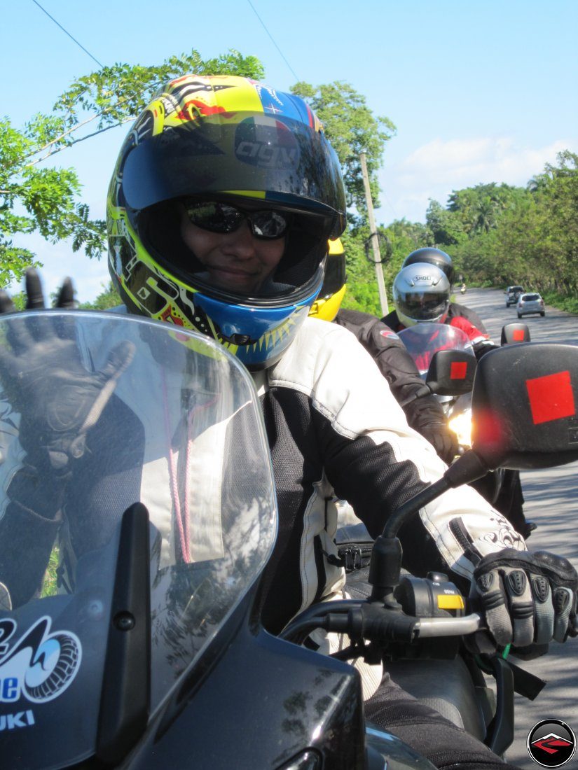 woman wearing a motorcycle helmet waving