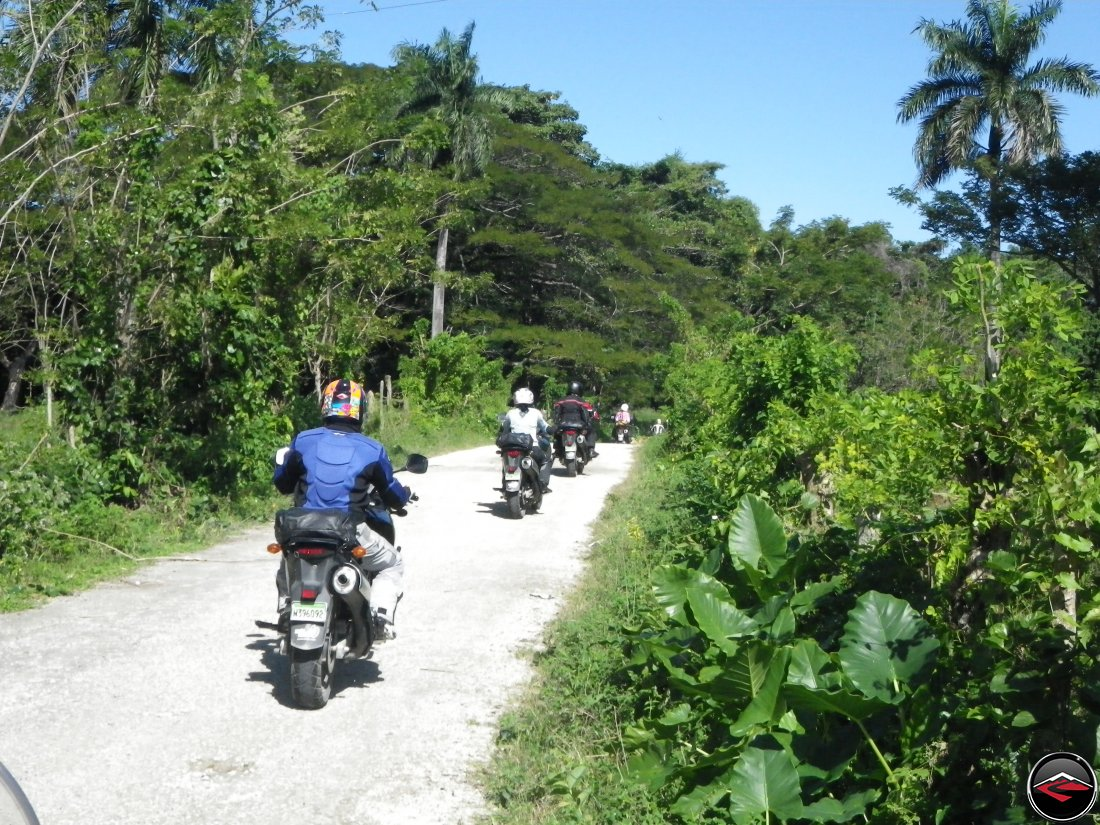 Suzuki V-Strom 650 motorcycles riding on a dirt road on a caribbean island