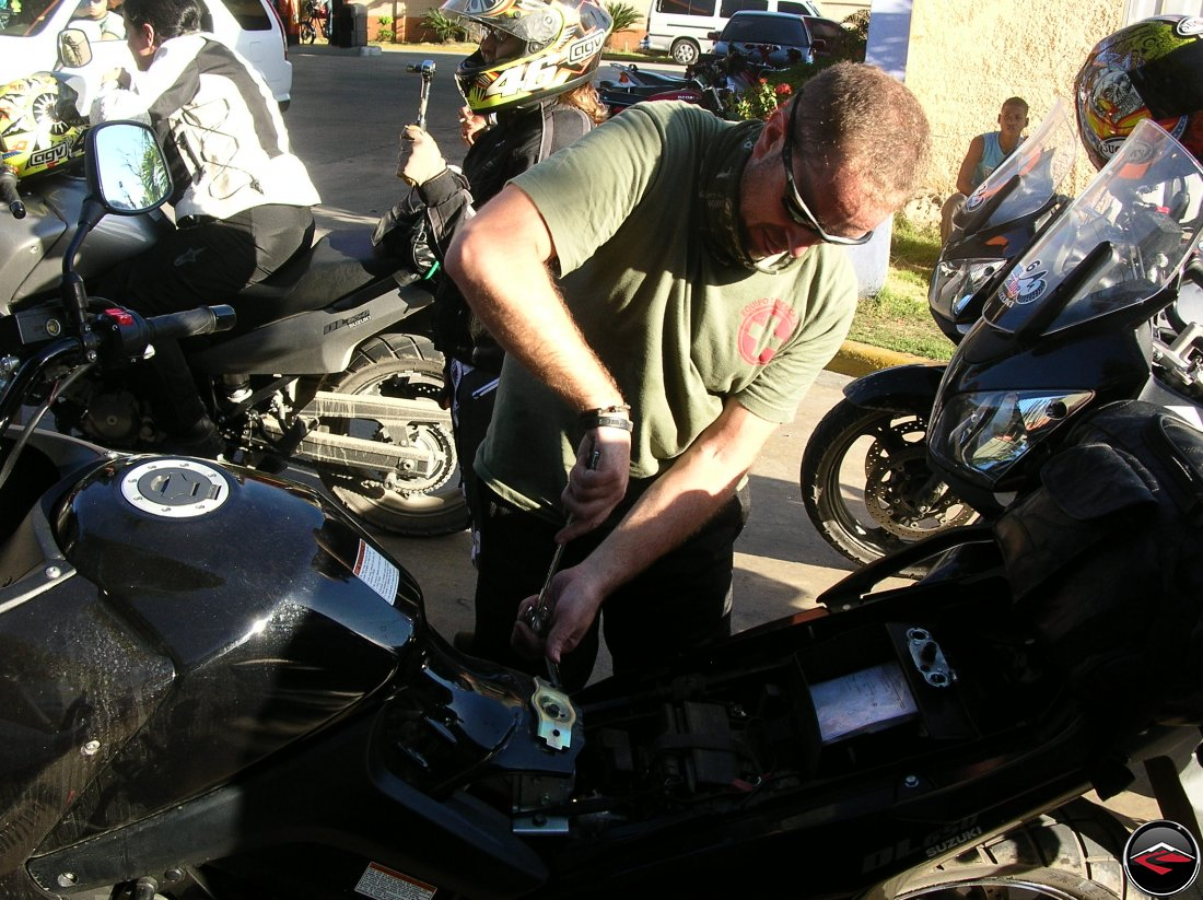 man using two-wrecnhes to tighten a bolt on a Suzuki V-strom 650 motorcycle