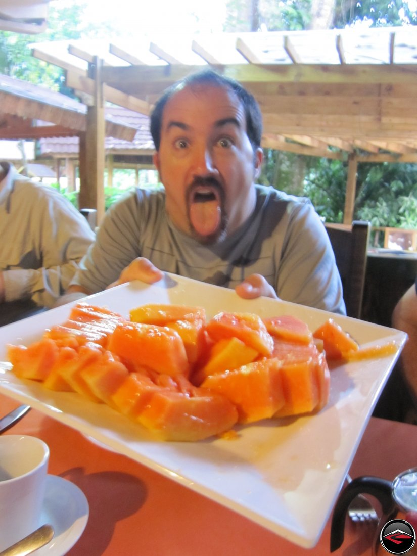 man holding a plate of papaya