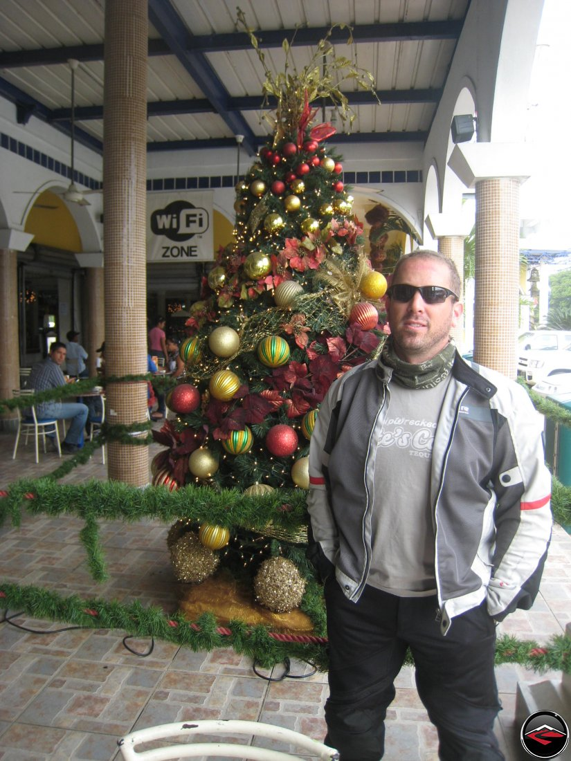 man standing in front of a christmas tree