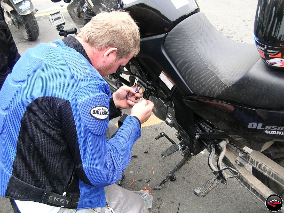 Man modifying the wiring on a Suzuki V-Strom 650 motorcycle in a parking lot