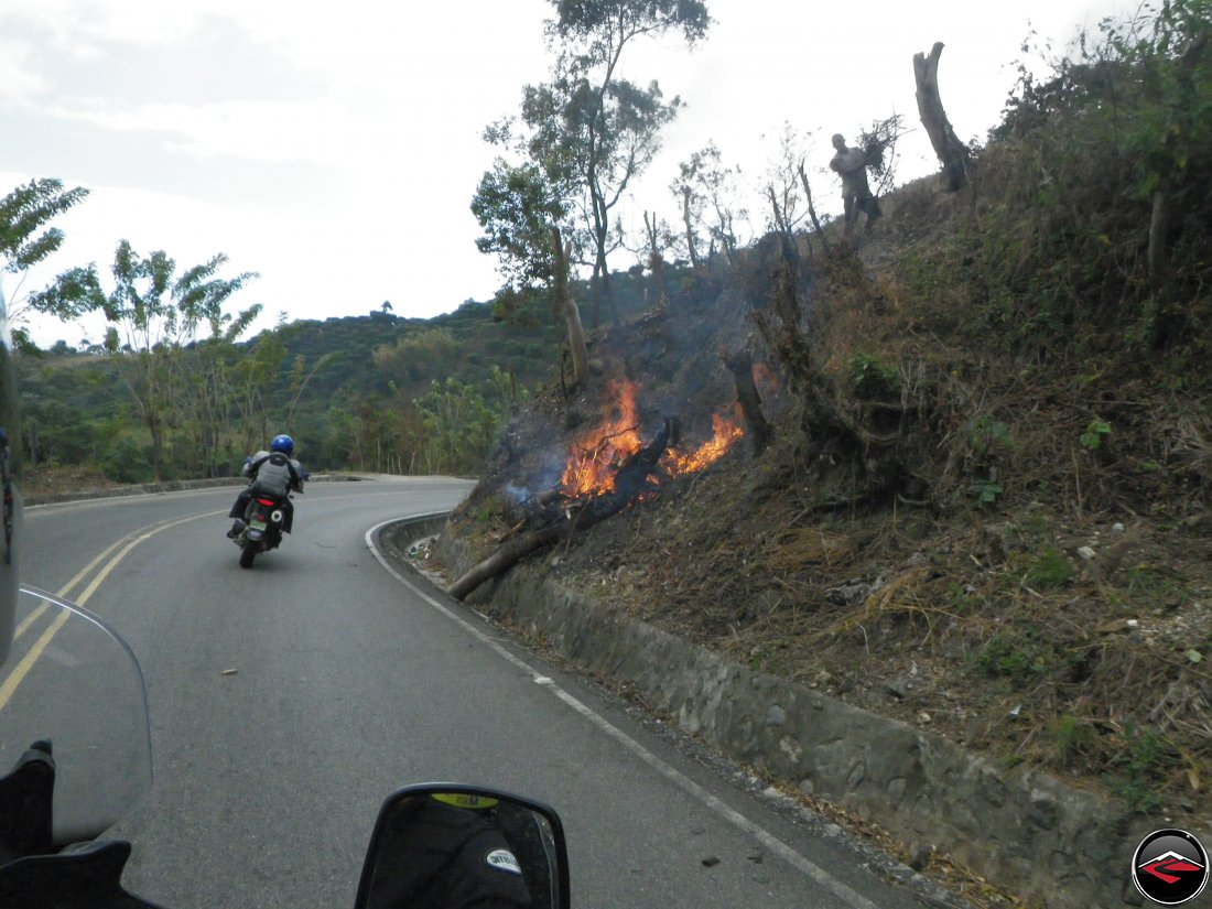 motorcycle riding around a corner past a burning tree on the side of the road