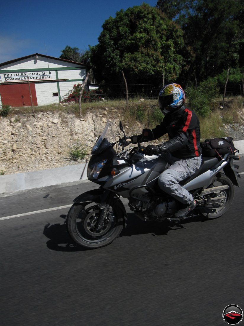 CanyonChaser Ryan man riding a motorcycle past a barn, frutales cabi, s.a. dominican republic