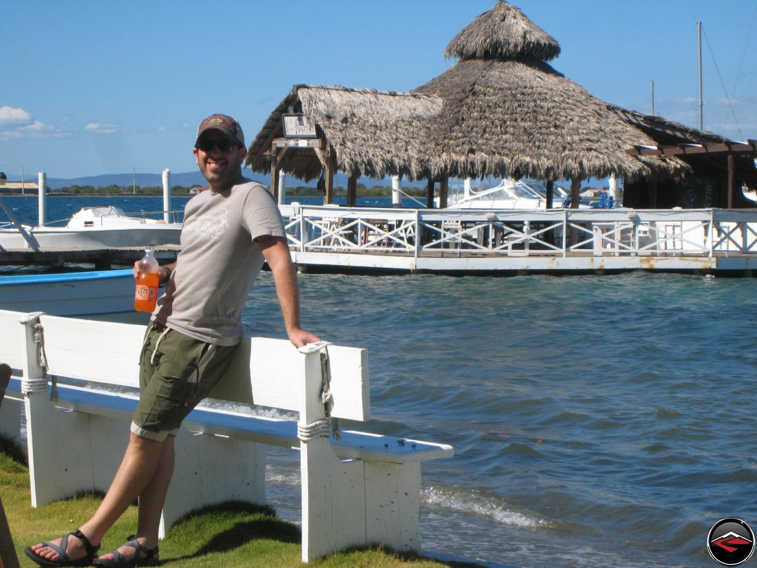 Man drinking orange fanta in front of thatched roof cabana