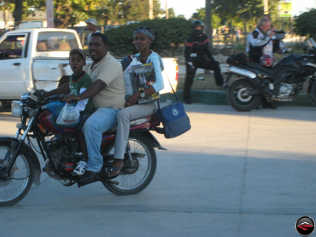three people on a small motorcycle, mother, father and son, with mom carrying a toy transformer