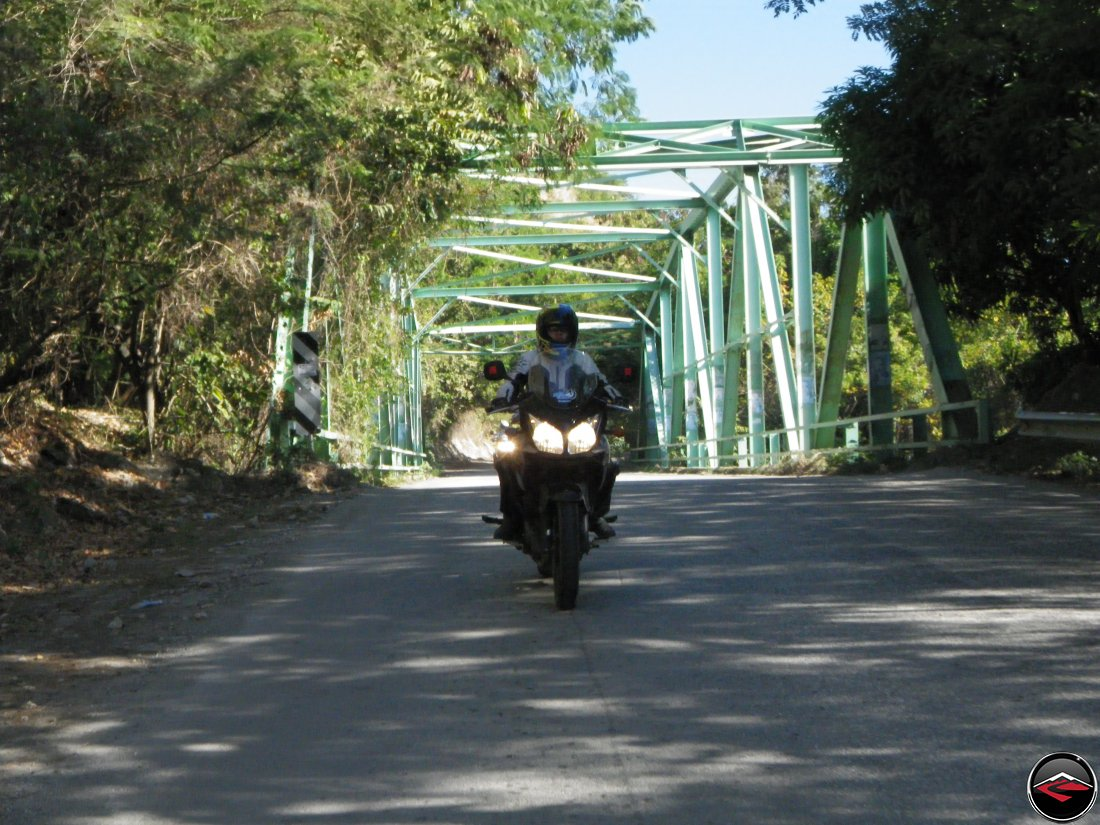 woman riding a motorcycle over a steel trellis bridge