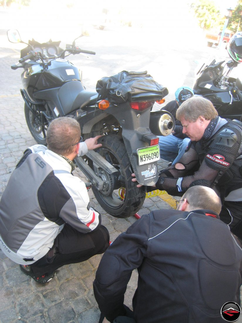 three men work on fixing a flat motorcycle tire