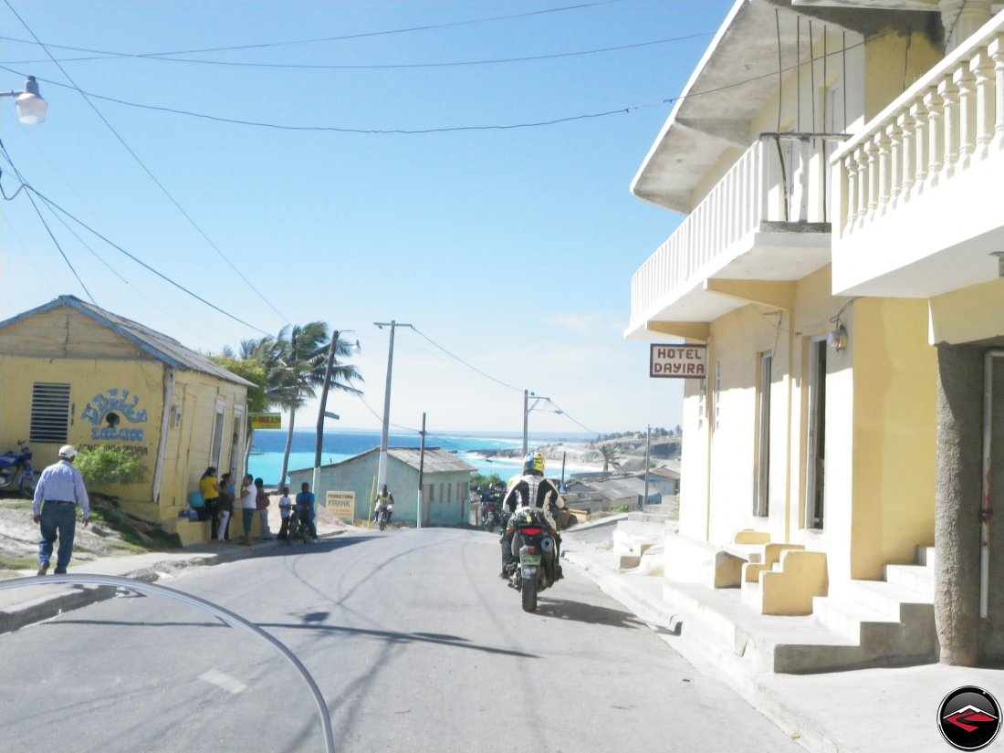 woman riding a motorcycle past caribbean hotel dayira