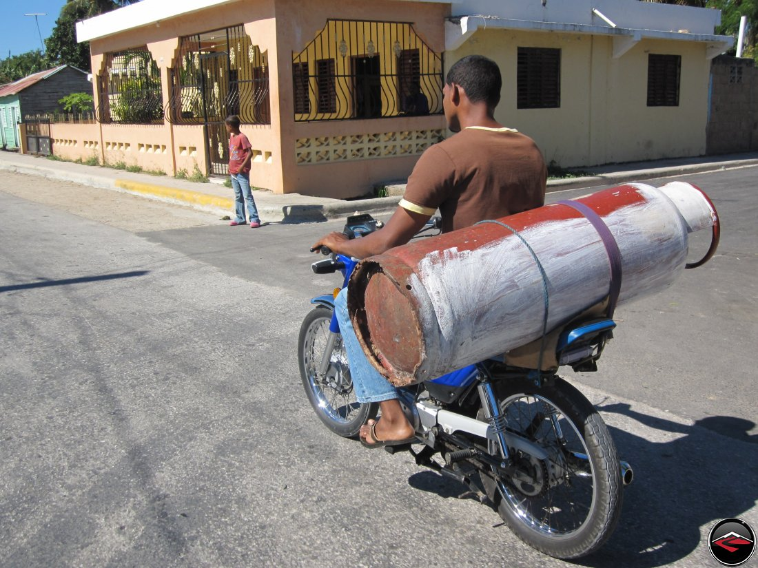 man hauling massive propane tank on motorcycle