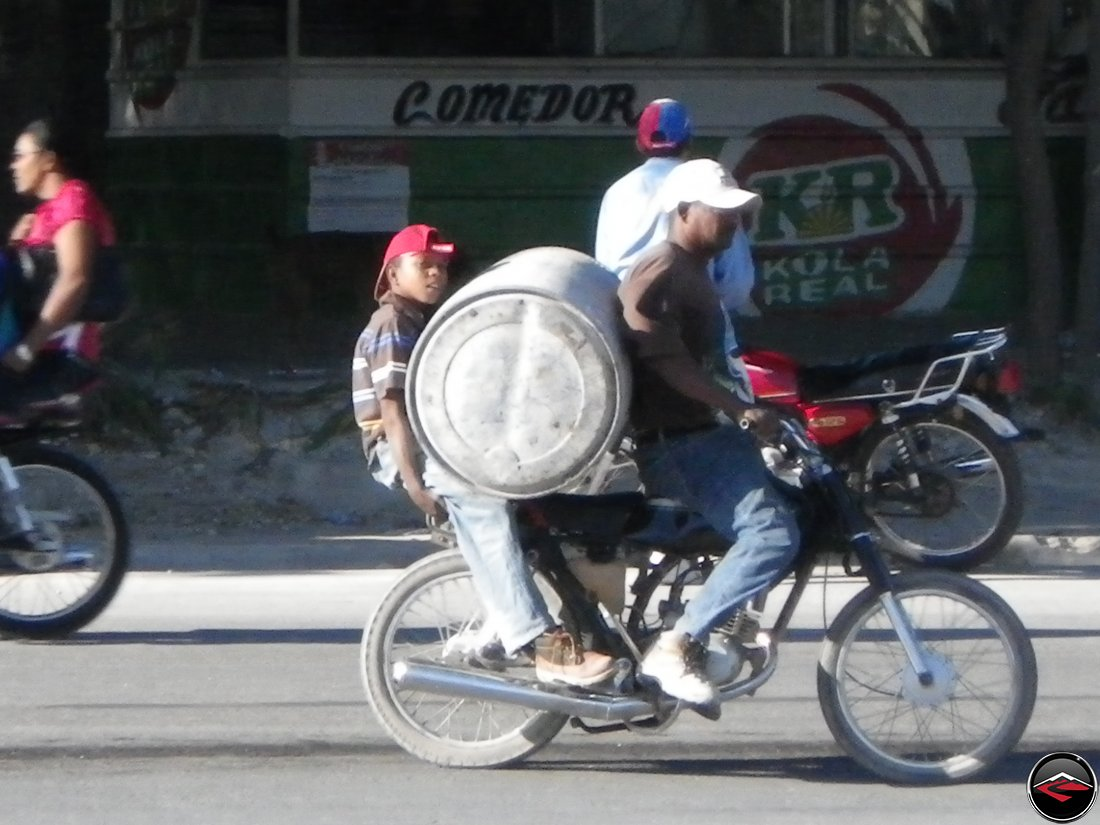 man and boy hauling massive barrel on a motorcycle
