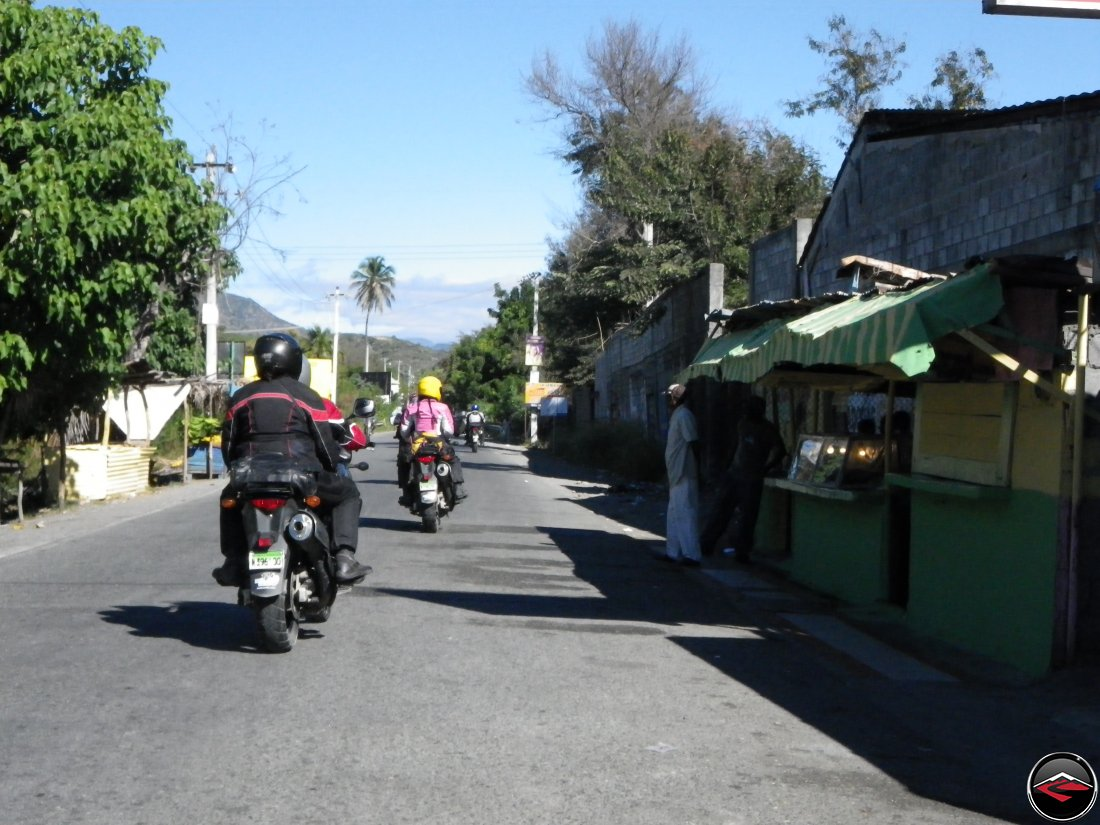 motorcycles riding past caribbean homes and businesses right off the side of the road