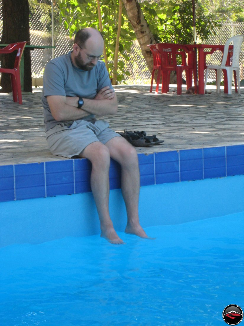 grumpy man looking miserable while soaking his feet in a pristine swimming pool