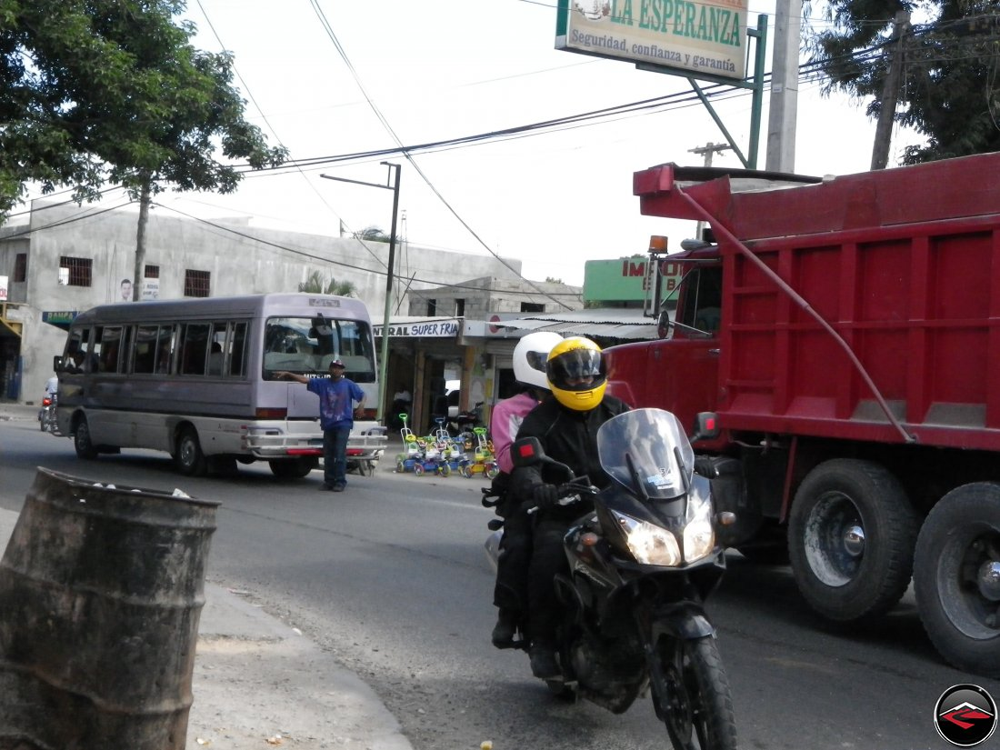 motorcycle riding around a city corner in the dominican republic, la esperanza, seguridad, confianza y garantia