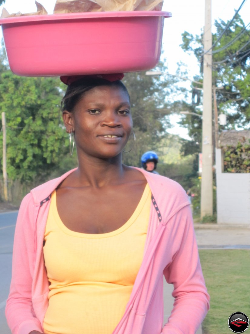 woman carrying heavy pink bucket on her head