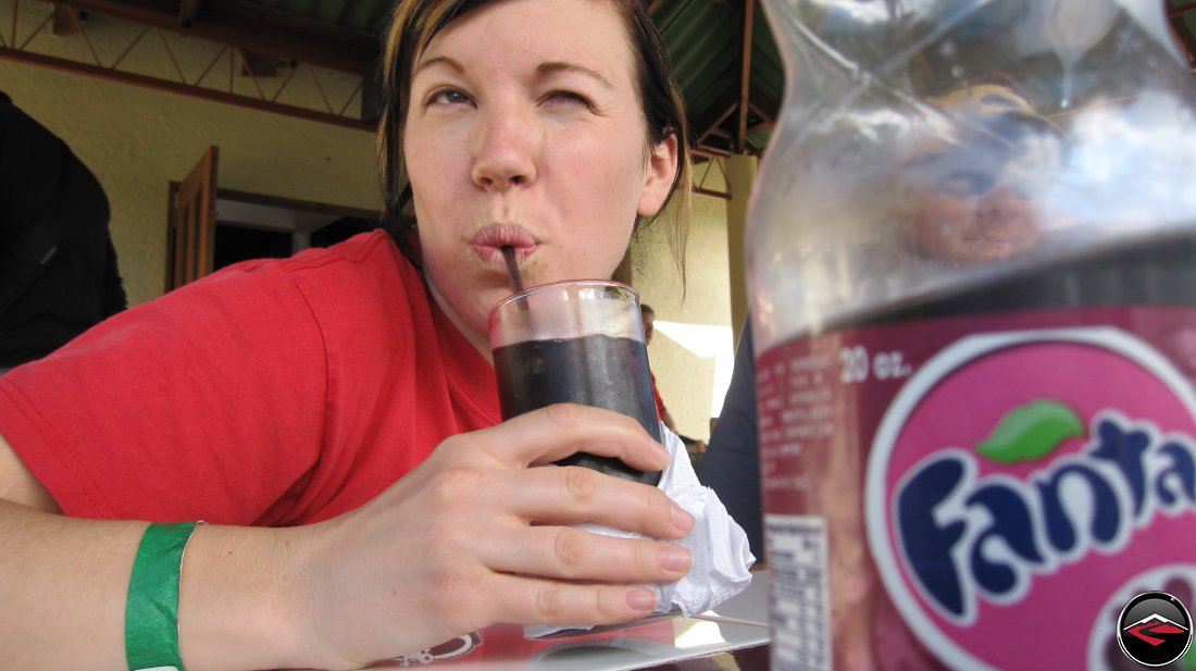 Pretty girl making a funny face while drinking grape fanta soda through a straw