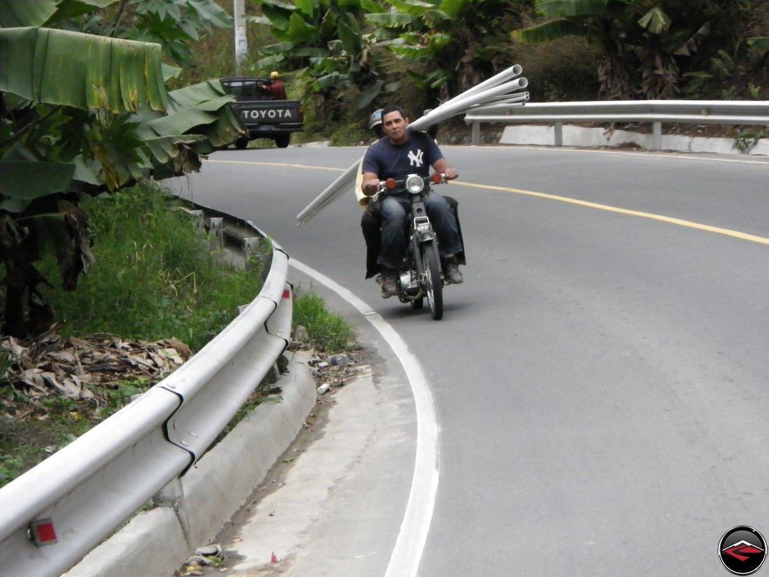 Two men on a motorcycle carrying long PVC pipe