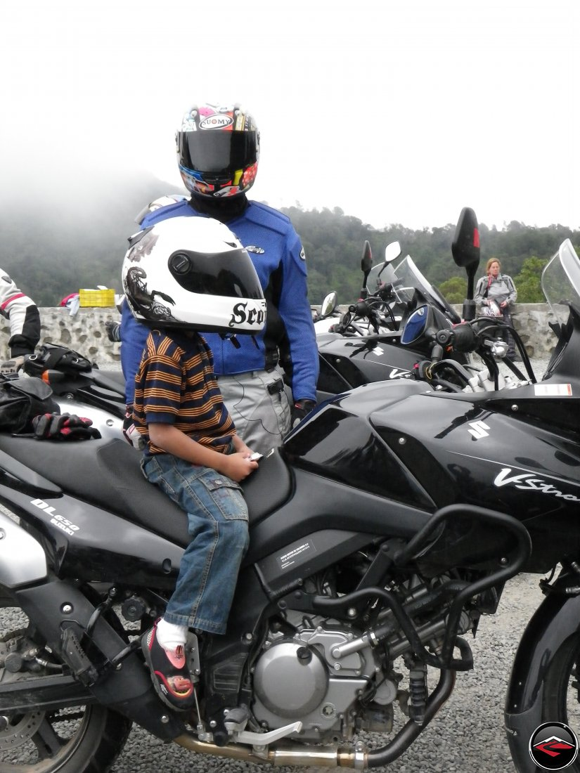 Man in a suomy helmet with a young boy sitting on a motorcycle wearing a scorpion helmet
