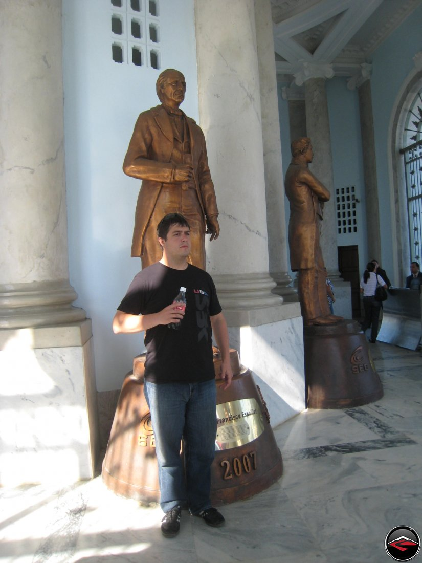 man mimicking copying the statue behind him