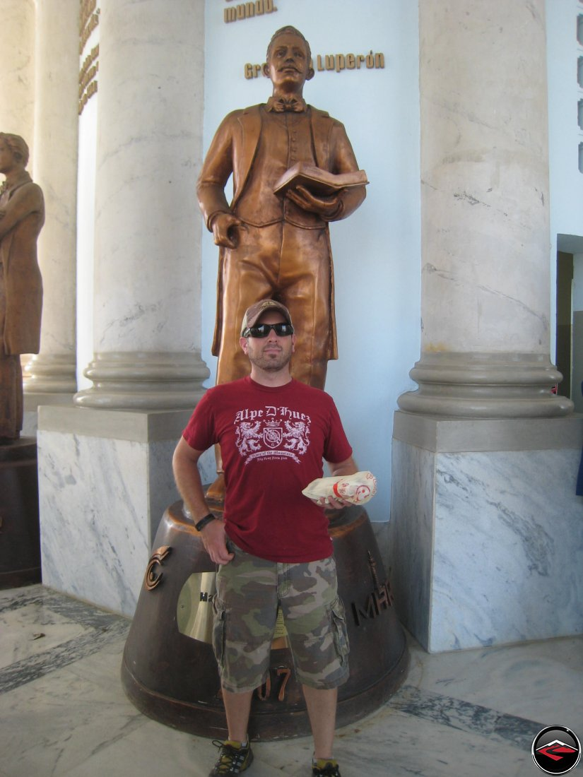 man mimicking copying the statue behind him holding a sandwhich