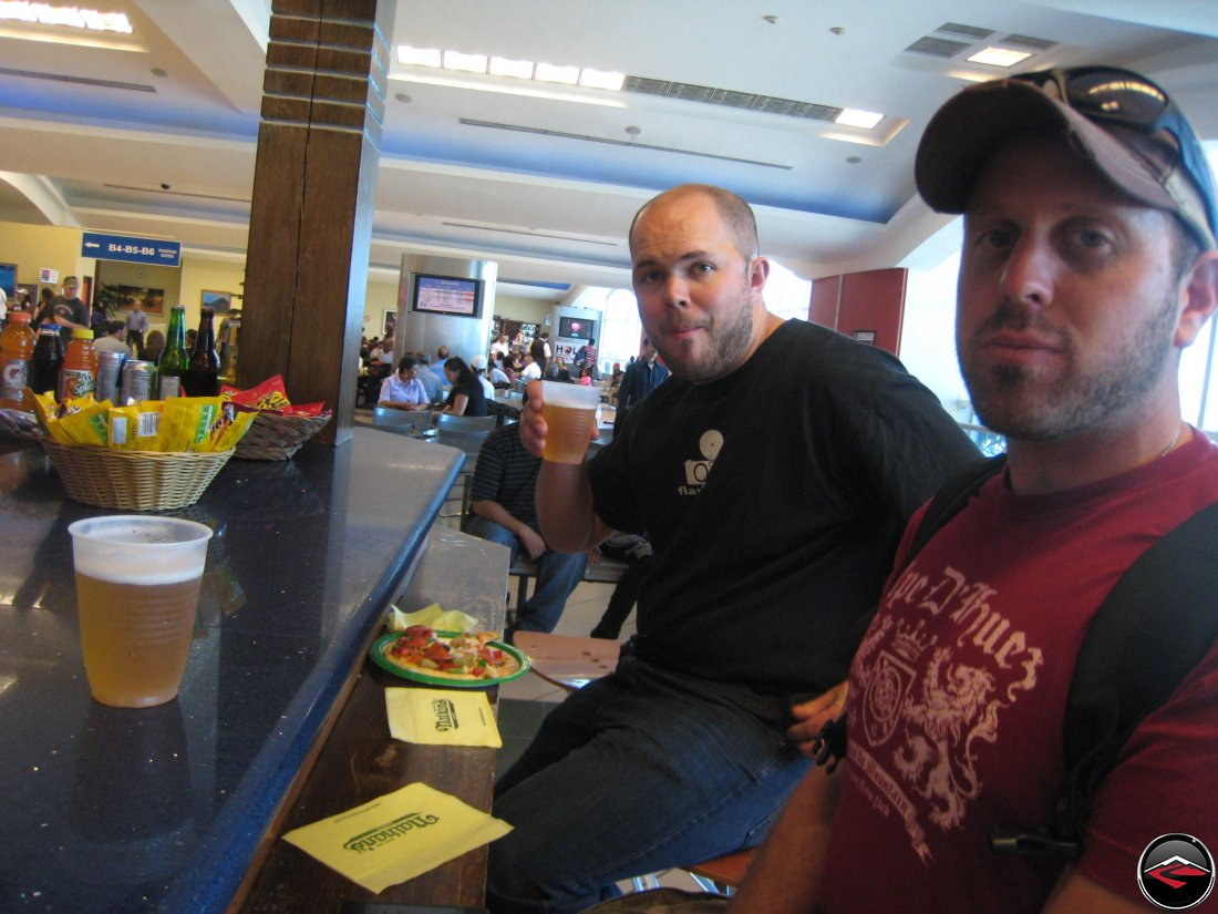 two men drinking beer at an airport