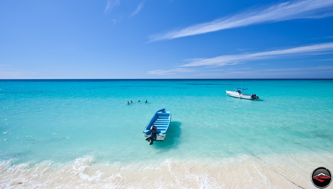 four people swimming in the perfect caribbean waters on a white sandy beach