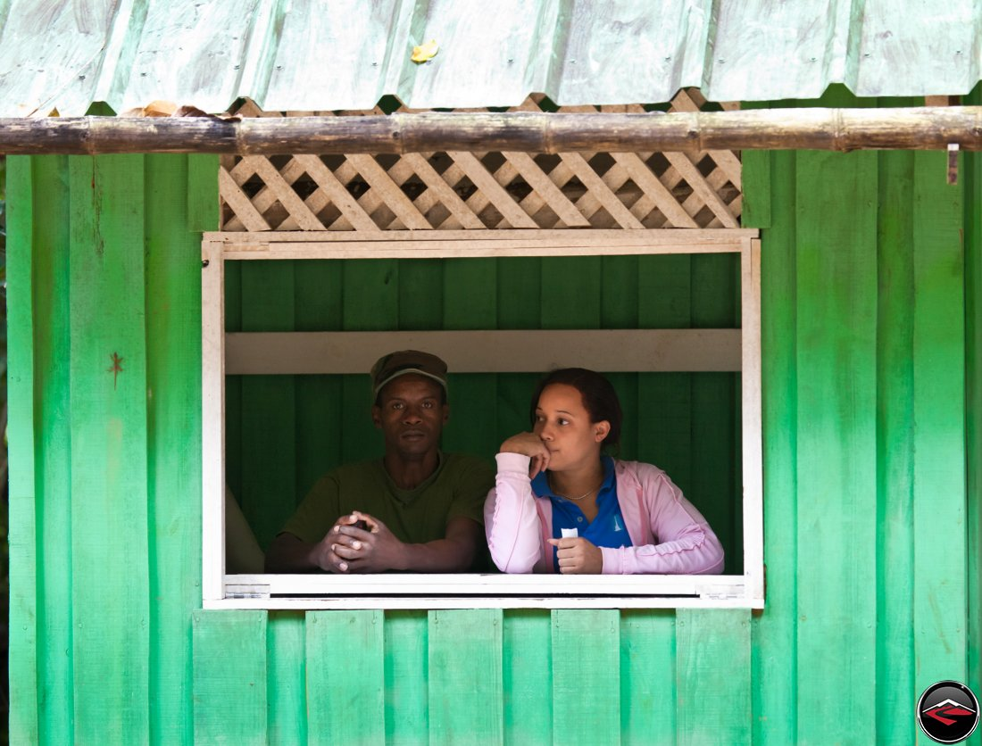 Man and woman look out the window of a green shack in the dominican republic on a caribbean island
