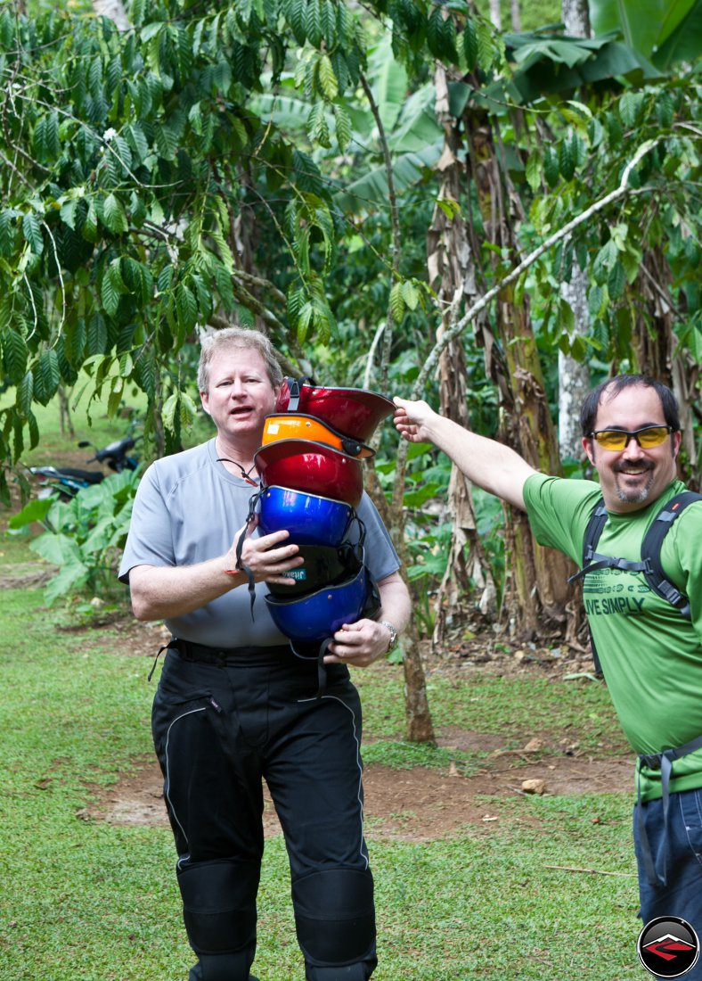 man holding a stack of silly, colorful helmets Cascada El Limon Dominican Republic