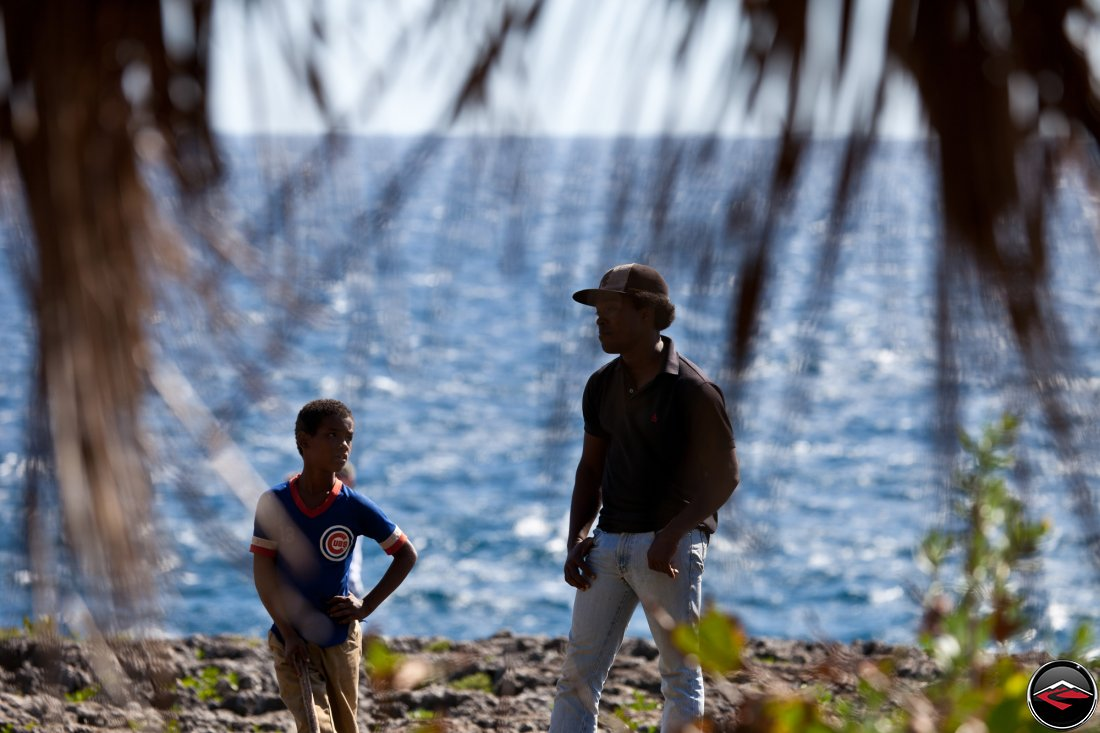 local dominican republic man and boy standing near the ocean