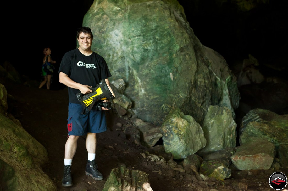 Man standing in a cave holding an extremely large flashlight
