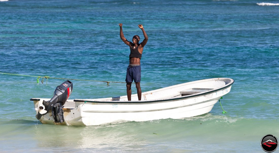 grateful dominican republic man standing in a boat on the caribbean ocean