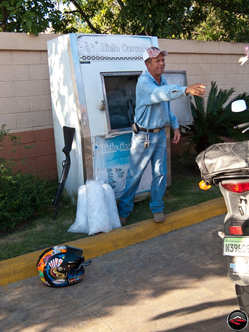 dominican republic gas station guard leans his shotgun against the wall to sell ice