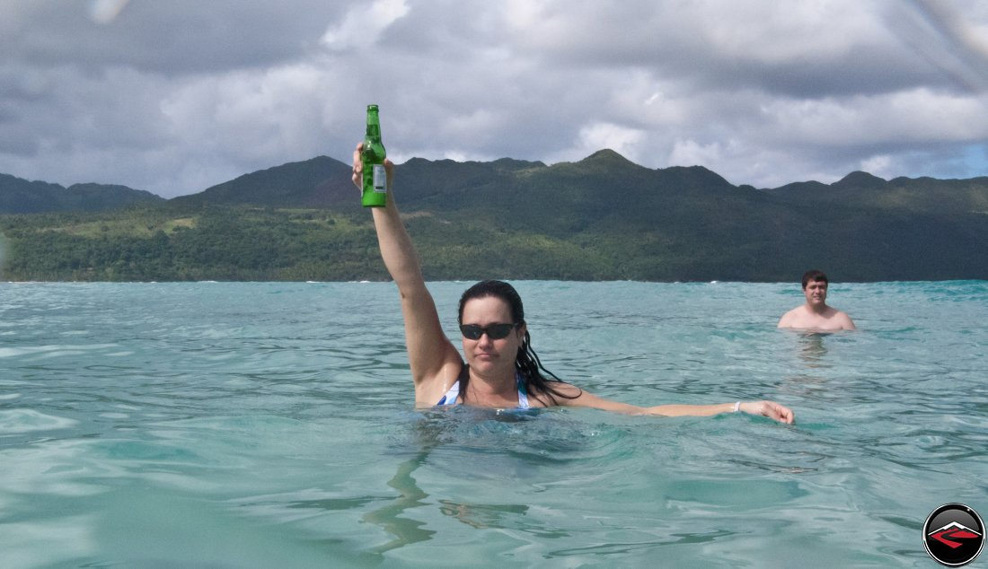 woman holding a presidente Beer in the air while she stands in the water Playa Rincon Dominican Republic