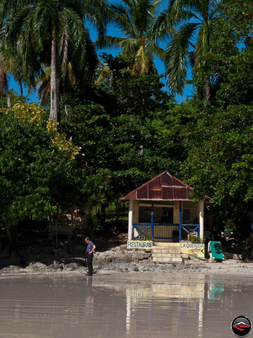 man standing on the beach in front of la querida restaurant in the dominican republic
