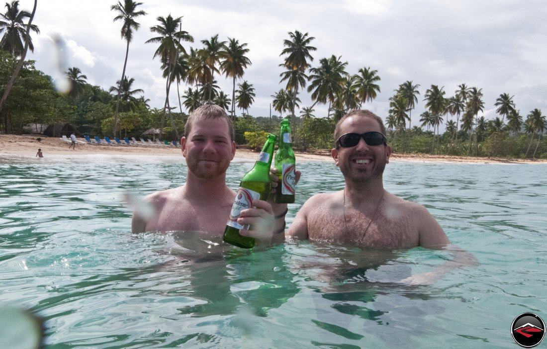 Two men drinking presidente beer while standing in caribbean ocean water Playa Rincon Dominican Republic