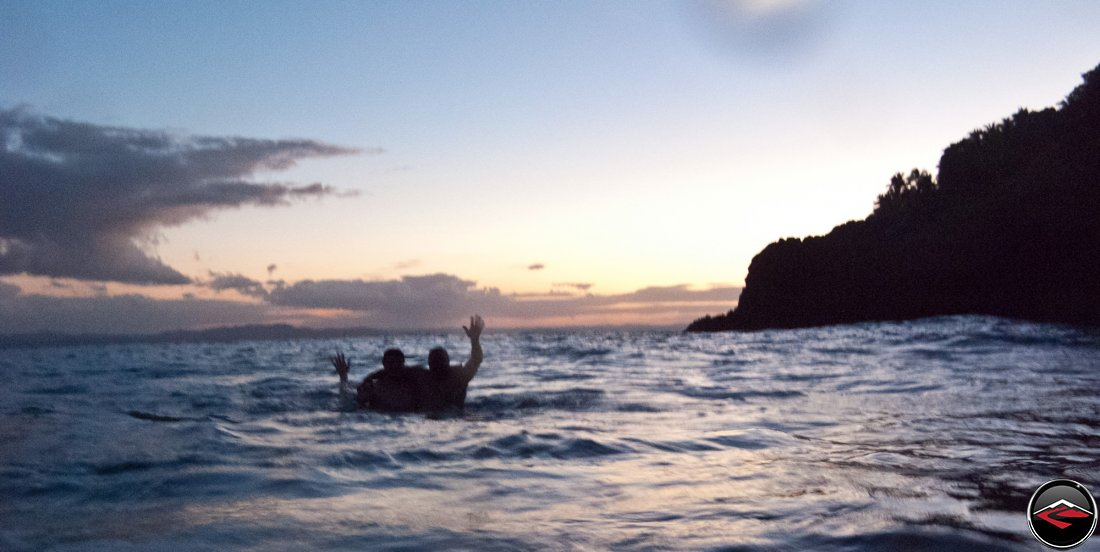 silhouette of two men in the ocean waving to the camera at sunset La Tambora Beach Resort