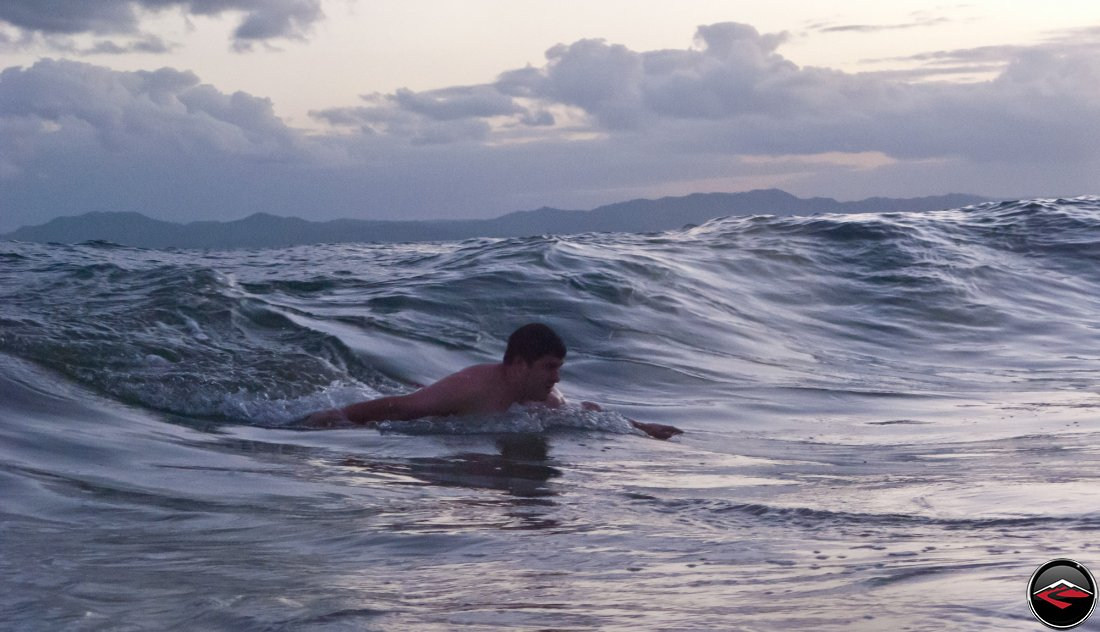 Man body surfing in the ocean La Tambora Beach Resort